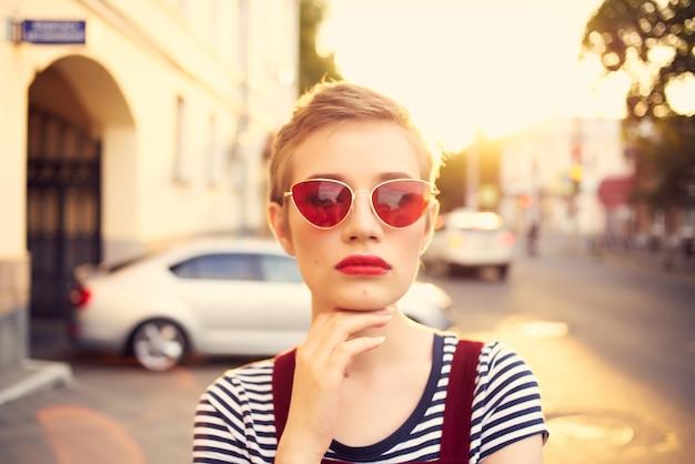 Vrouw met een zonnebril die door het zomerhuis van de stad loopt