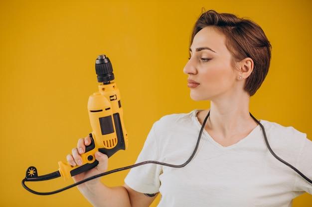 Vrouw met elektrische boor op gele achtergrond