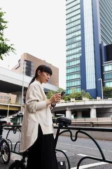 Vrouw met elektrische fiets in de stad die smartphone gebruikt