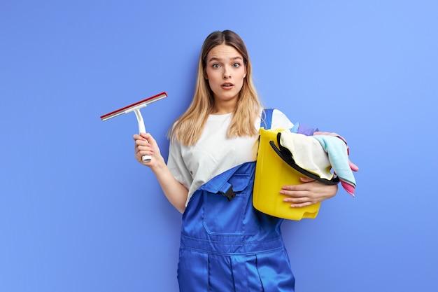 Vrouw met emmer met groep schoonmaakproducten. jonge dame in overall staat in shock door vuil