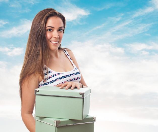 Vrouw met enkele groene dozen in handen