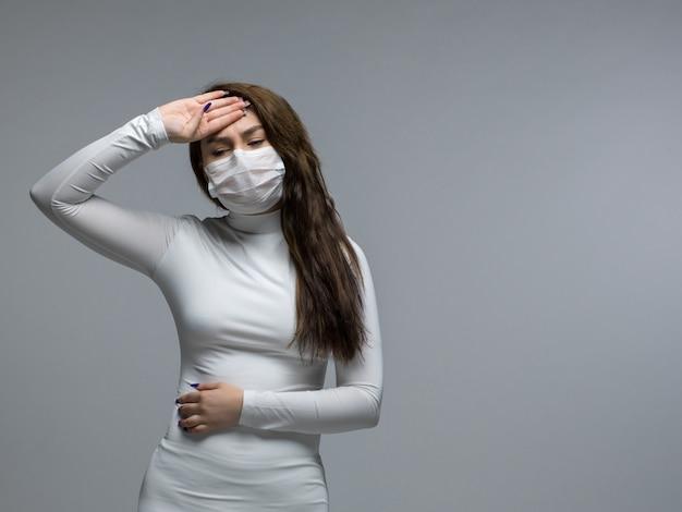 Vrouw met ernstige hoofdpijn die haar voorhoofd in wit beschermend masker houdt