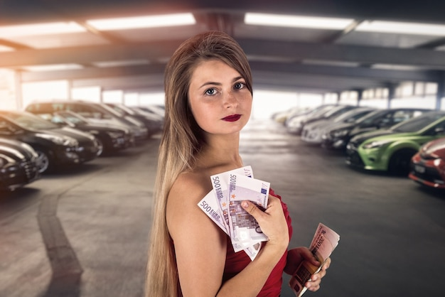 Vrouw met eurobankbiljetten in garage auto kopen