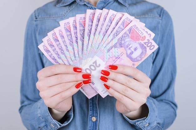 Vrouw met fan van tweehonderd oekraïense hryvnia-bankbiljetten