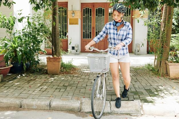 Vrouw met fiets die huis verlaat