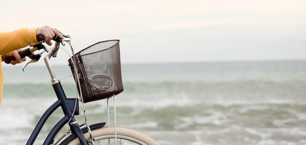 Vrouw met fiets en gele trui, zee met golven op de achtergrond, gedeeltelijk zicht, ruimte voor tekst.