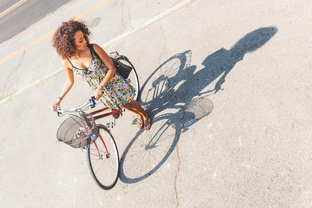 Vrouw met fiets met haar schaduw op de weg.