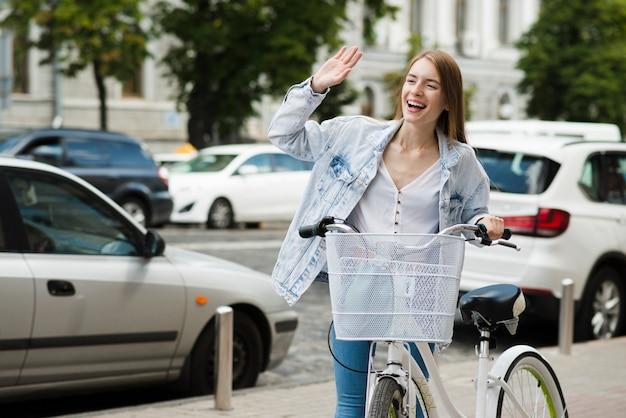 Vrouw met fiets zwaaien