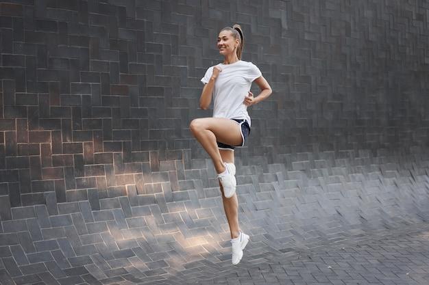 Vrouw met fit lichaam springen en rennen