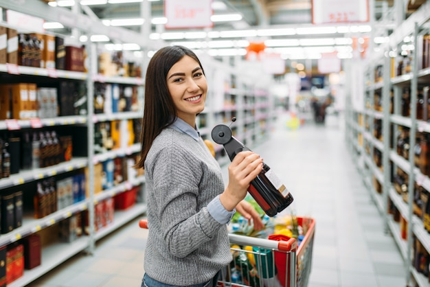 Vrouw met fles alcoholische drank in supermarkt, afdeling alcoholdranken, familie winkelen. vrouwelijke klant wijn kiezen in winkel, kopers in de markt