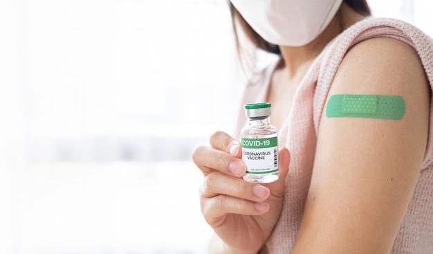 Vrouw met fles voor vaccinatie en toont haar arm met verband nadat ze is gevaccineerd, patiënten die maskers dragen om te worden gevaccineerd tegen covid-19, gezond en vaccinconcept
