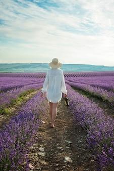 Vrouw met fles wijn op lavendelgebied