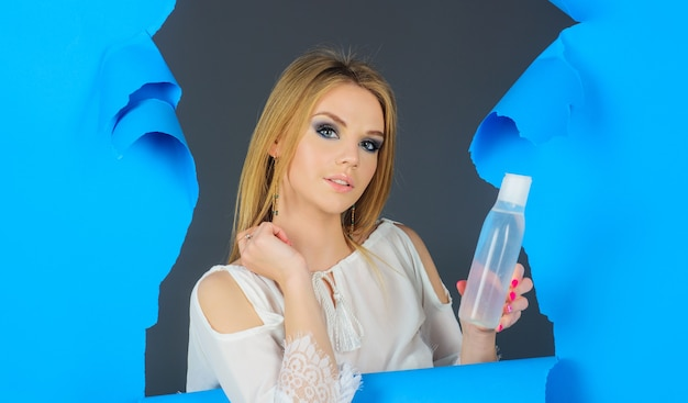Vrouw met flesje micellair water of face tonic. makeup verwijderaar. huidsverzorging. schoonheidsbehandeling.