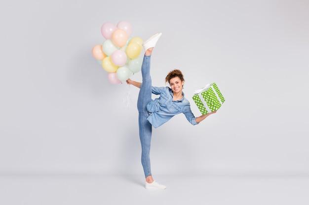 Vrouw met flexibele lichaamsvaardigheden die geschenk en ballonnen houden