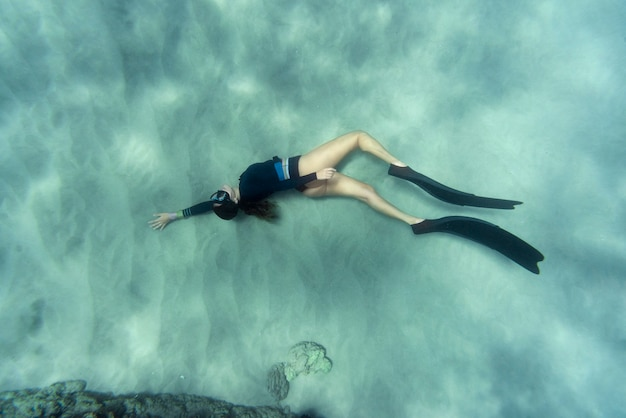 Vrouw met flippers die in de oceaan zwemmen