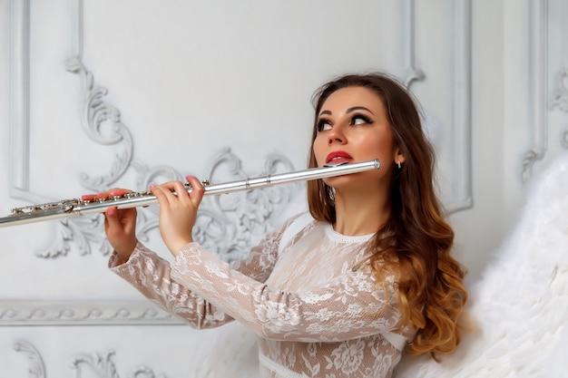 Vrouw met fluit en vleugels. meisjesactrice in pak met vleugels en fluitzitting. getextureerde muur op de achtergrond. het concept van muzikaal ontwerp. ruimte voor uw belettering of logo