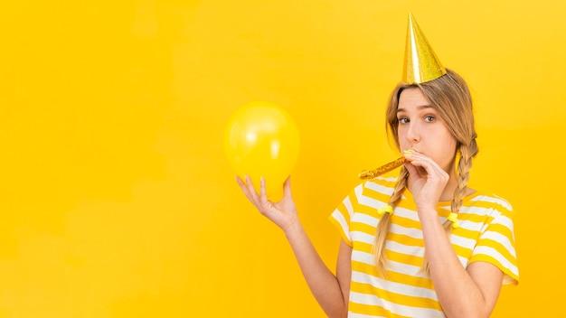 Vrouw met fluiterventilator en ballon