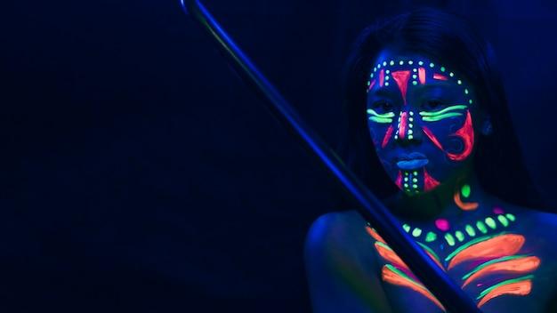 Vrouw met fluorescerende make-up en kopie ruimte