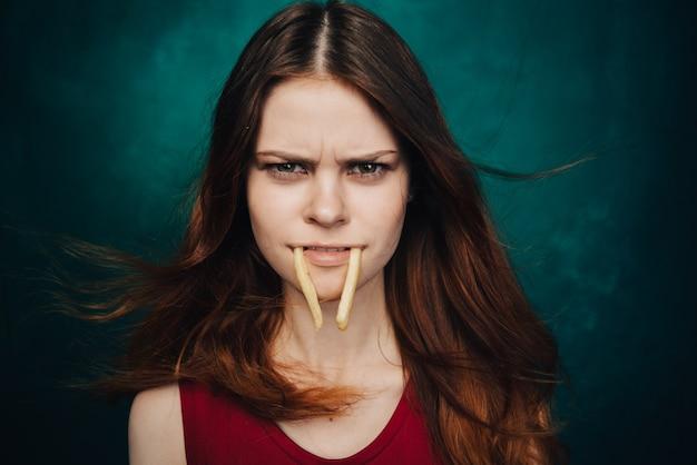 Vrouw met frietjes in haar tanden op een groen fastfood als achtergrond