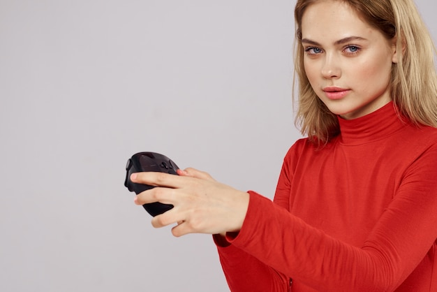 Vrouw met gamepad in handen spelen van spelletjes emoties levensstijl vrije tijd rood shirt licht