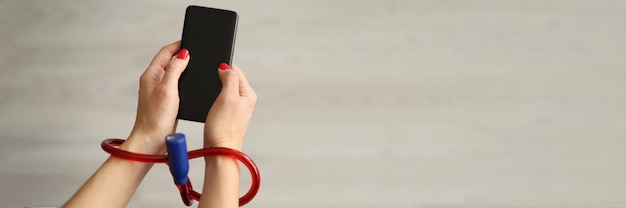 Vrouw met gebonden handen met mobiele telefoon close-up