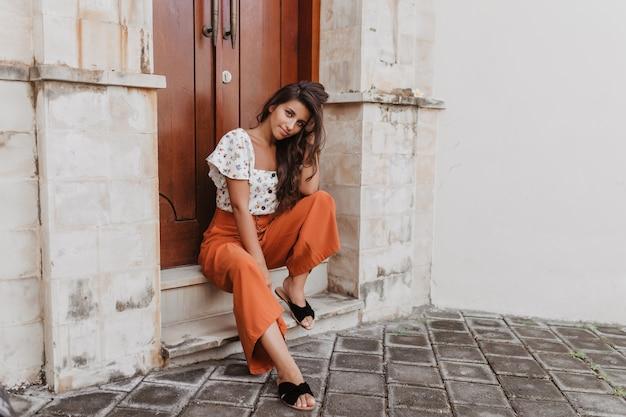 Vrouw met gebruinde huid in lichte zomer outfit poseren zittend op de drempel van het oude gebouw met mooie houten deur