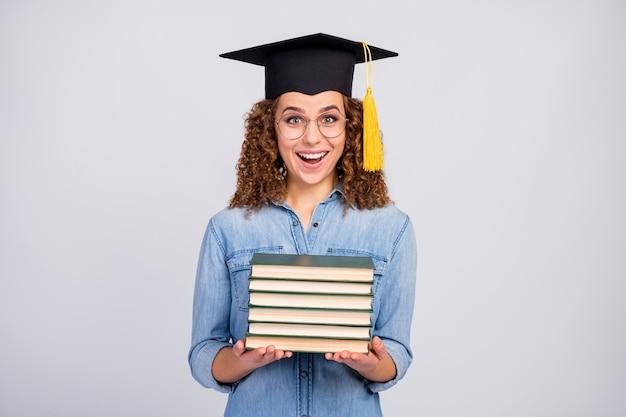 Vrouw met gediplomeerde hoed en stapel boeken