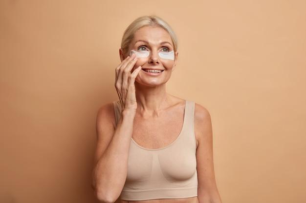 Vrouw met gekamd blond haar brengt collageenpleisters onder de ogen aan