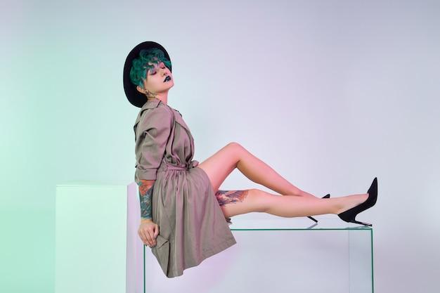Vrouw met gekleurd groen haar in een zwarte bodysuit poseert bij een glazen kubus, tatoeages op het lichaam van het meisje