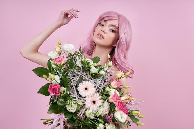 Vrouw met gekleurd roze sterk haar houdt een boeket mooie bloemen in haar handen. natuurlijk geverfd haar mooie make-up, sterke uitgroei