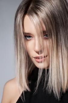 Vrouw met gekleurde haarkleur van een blonde. haar vrouw model in kleur ash kleur.