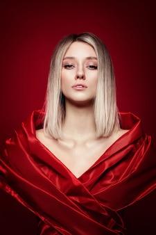 Vrouw met gekleurde haarkleur van een blonde in rode jurk op rode achtergrond. kleurend blond haarvrouwmodel in askleur