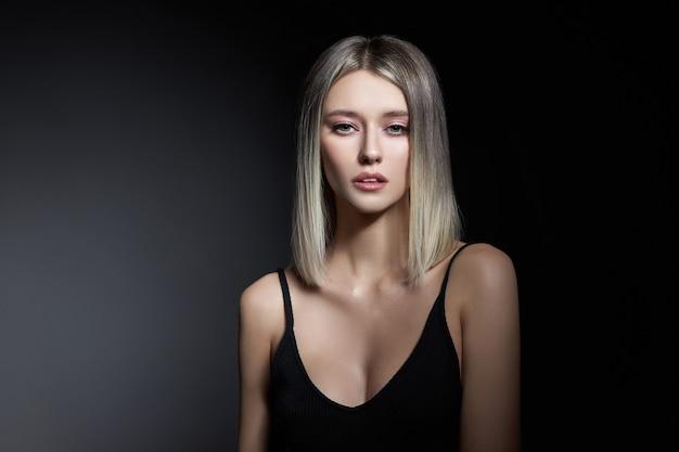 Vrouw met gekleurde haarkleur van een blonde op zwarte achtergrond. kleur haar vrouw model in ash kleur