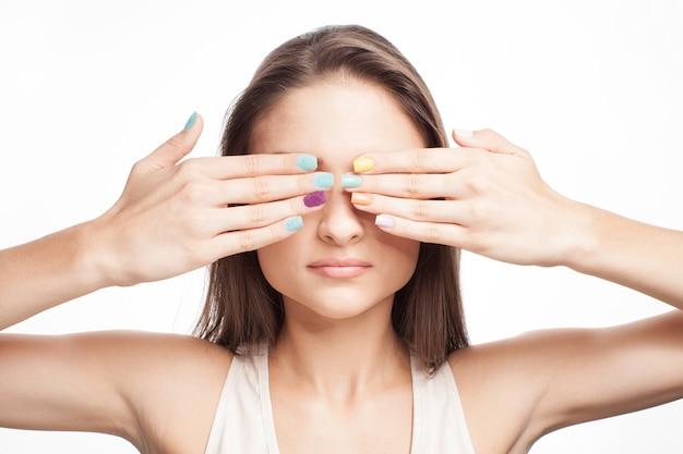 Vrouw met gekleurde nagels met haar handen voor het oog