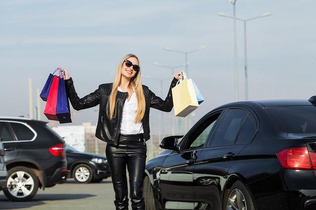 Vrouw met gekleurde zakken in de buurt van haar auto