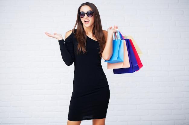 Vrouw met gekleurde zakken op ligth muur