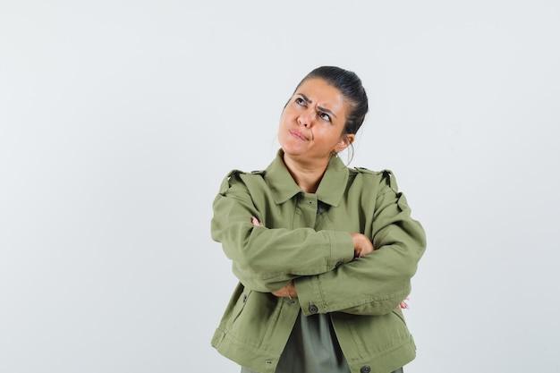 Vrouw met gekruiste armen in jas, t-shirt en peinzend op zoek