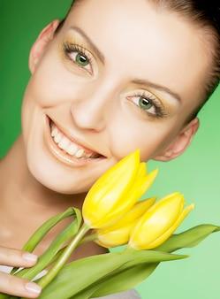Vrouw met gele bloemen op groen