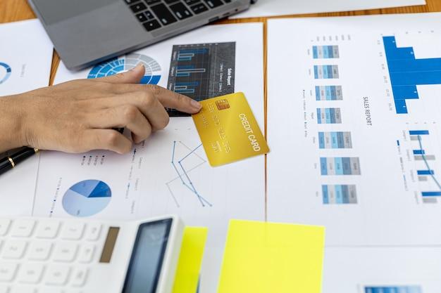 Vrouw met gele creditcard op bureau, creditcard geplaatst op financiële documenten, creditcard om online te betalen voor goederen en diensten. creditcard uitgaven concept.