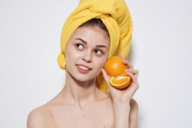 Vrouw met gele handdoek op haar hoofd blote schouders fruit oranje vitamine