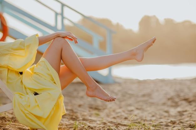 Vrouw met gele jurk met lange slanke benen met strand bij zonsondergang achtergrond