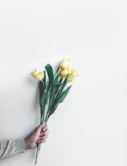 Vrouw met gele tulp op wit, bovenaanzicht