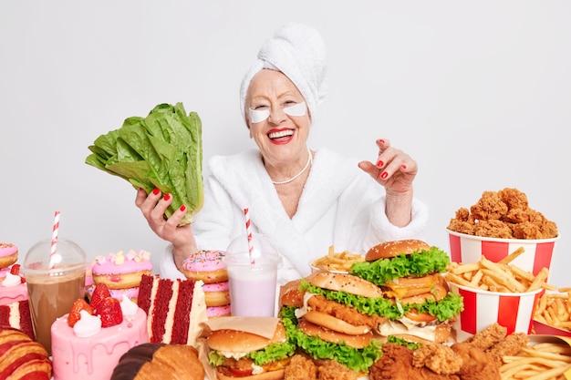 Vrouw met gerimpeld gezicht brengt schoonheidspleisters aan om wallen en wallen te verminderen leidt gezonde levensstijl houdt zich aan dieet weigert junkfood gekleed in badjas en handdoek op hoofd gewikkeld