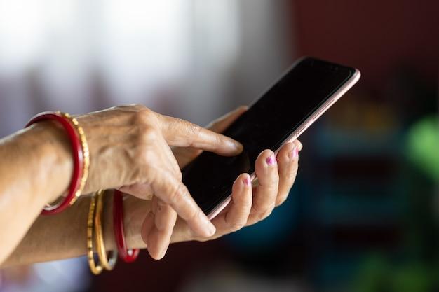Vrouw met gerimpelde handen die een smartphone gebruikt met een wazige achtergrond
