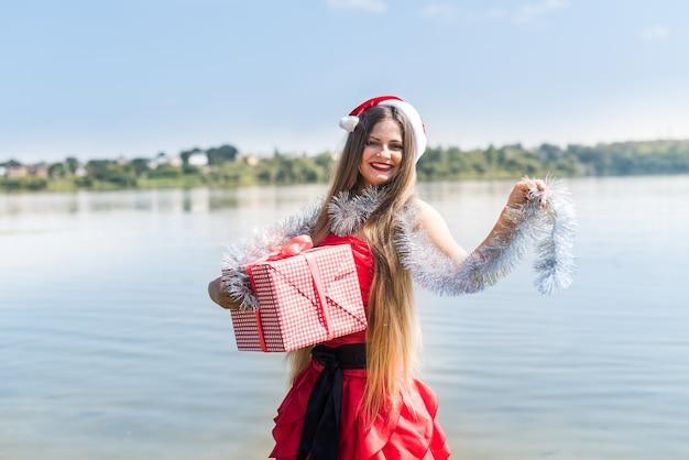Vrouw met geschenkdoos en guirlande poseren op de wal