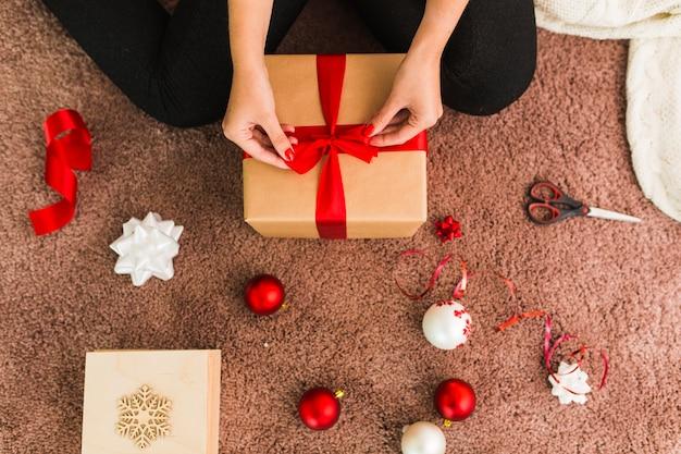Vrouw met geschenkdoos in de buurt van bogen, kerstballen en een schaar