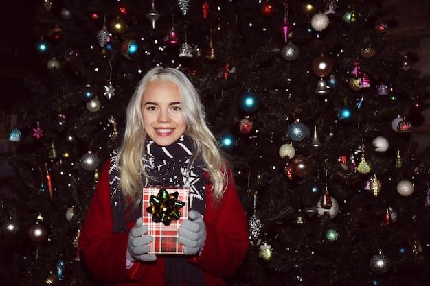 Vrouw met geschenkdoos op kerstmarkt