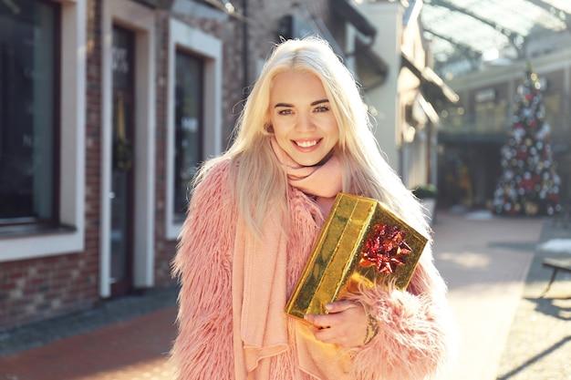 Vrouw met geschenkdoos op straat