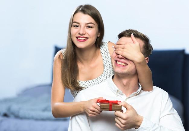 Vrouw met geschenkdoos voor man ogen
