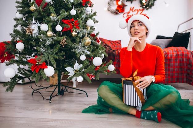 Vrouw met geschenken door kerstboom